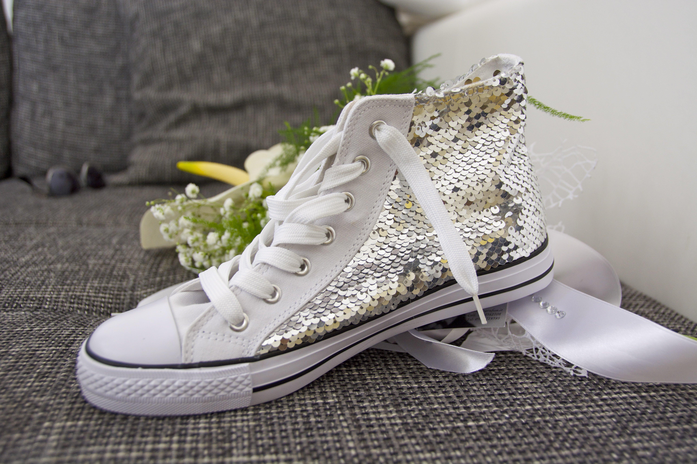 dettaglio scarpa sportiva bianca su un bouquet da sposa
