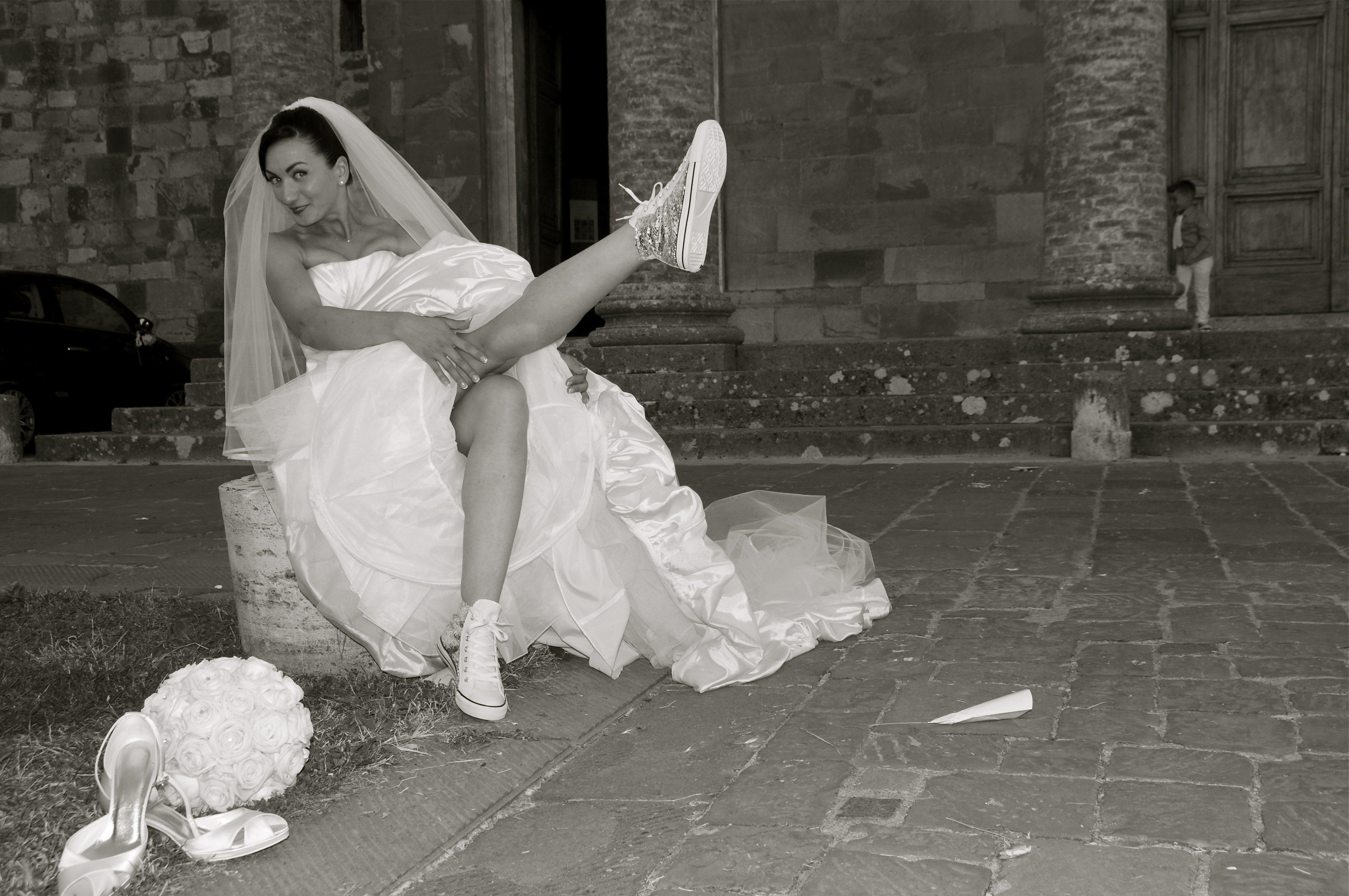 una sposa seduta che mostra scarpe sportive