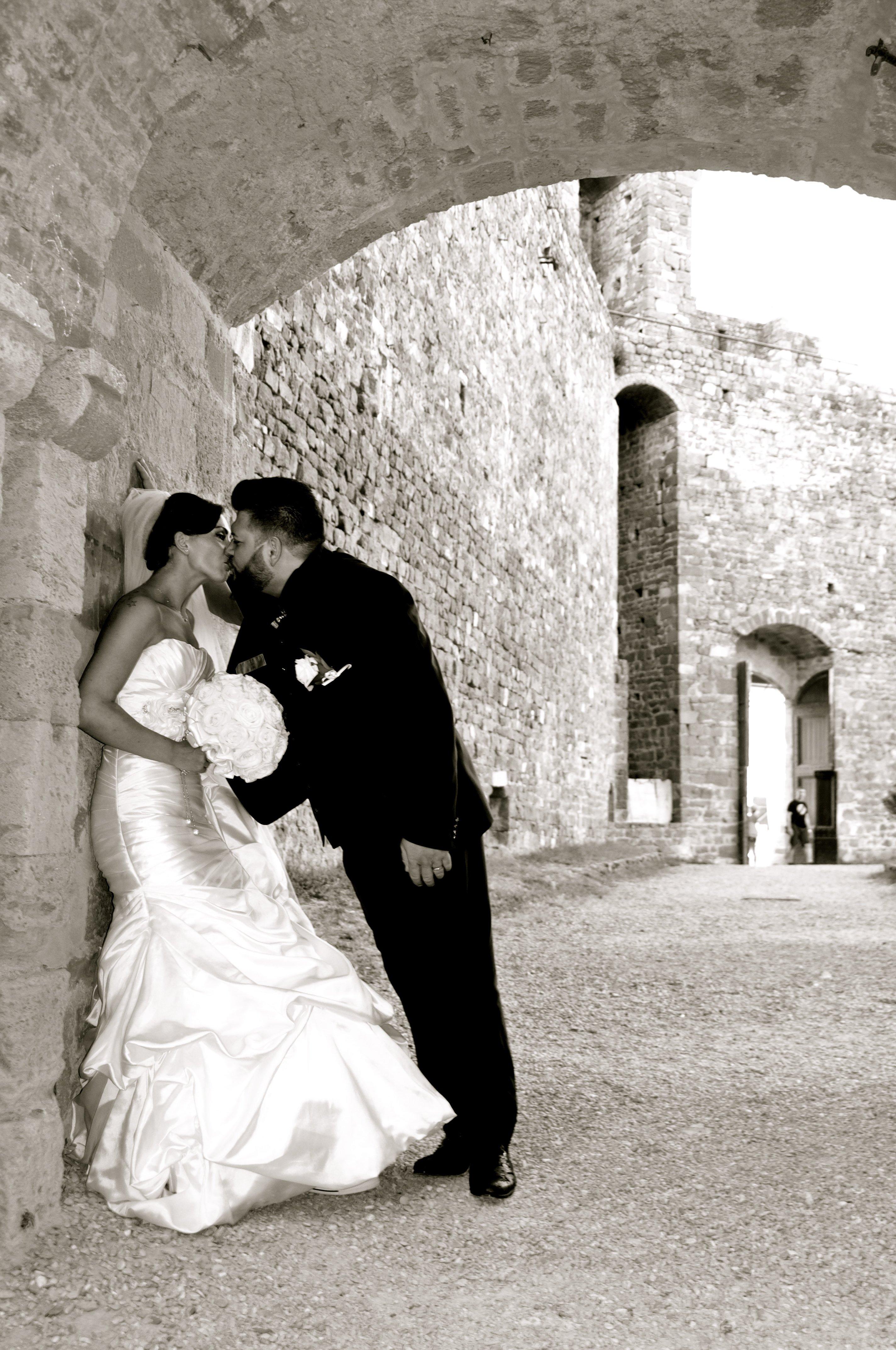sposo che bacia la sposa poggiata a un muro in strada