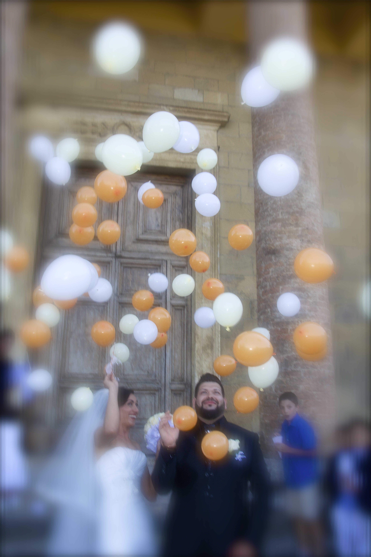 lancio di palloncini bianchi e arancioni per degli sposi