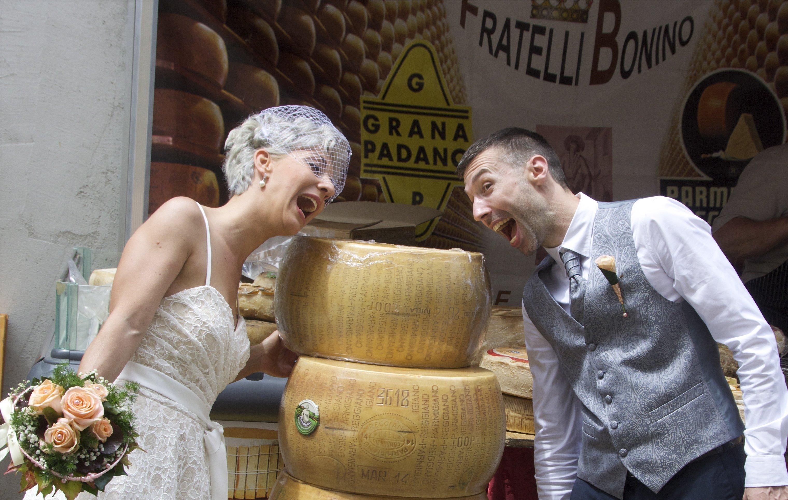 due sposi sorridenti che simulano di mordere delle forme di grana padano