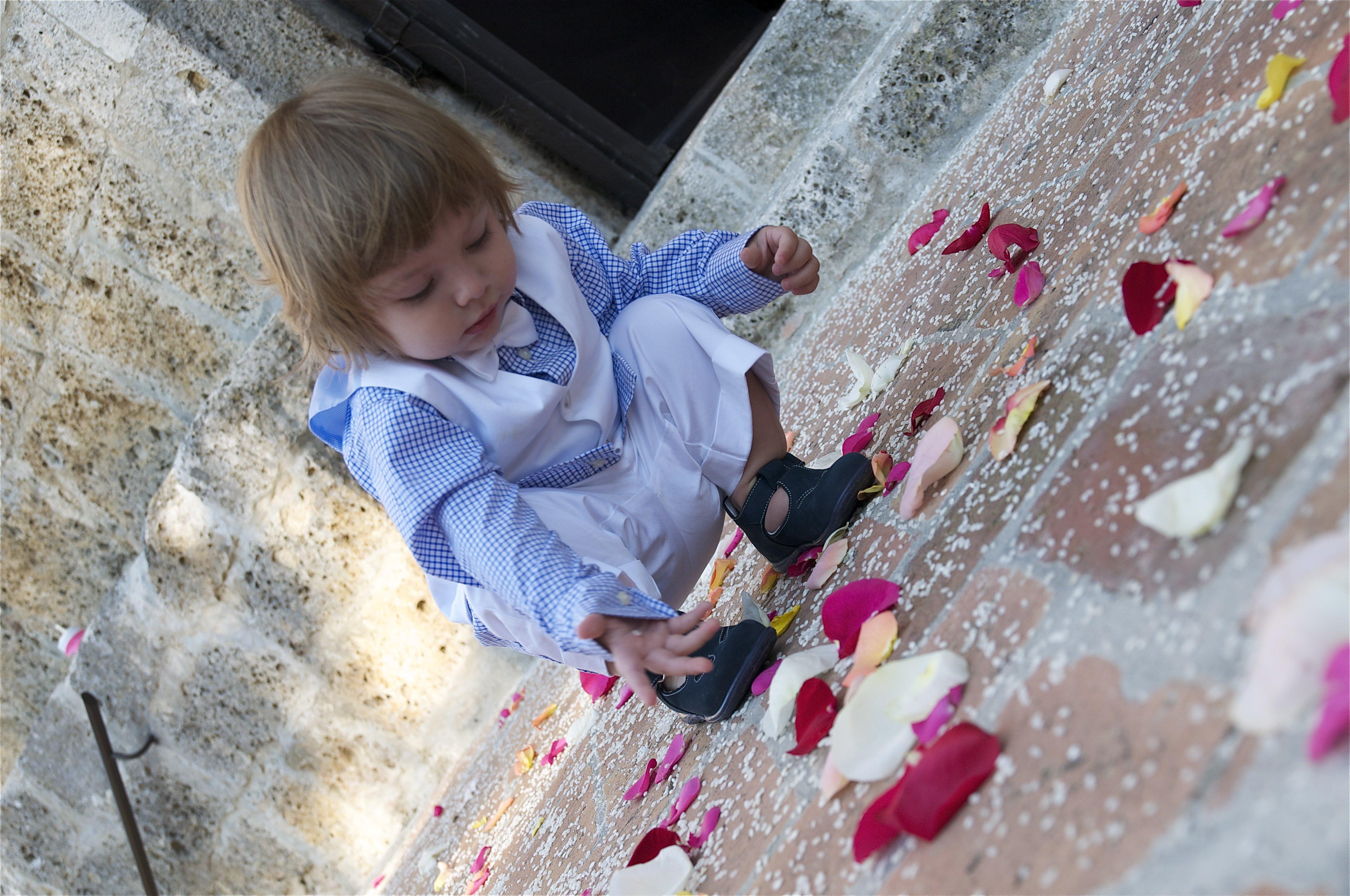 bambina raccoglie petali di rosa all'uscita di una chiesa