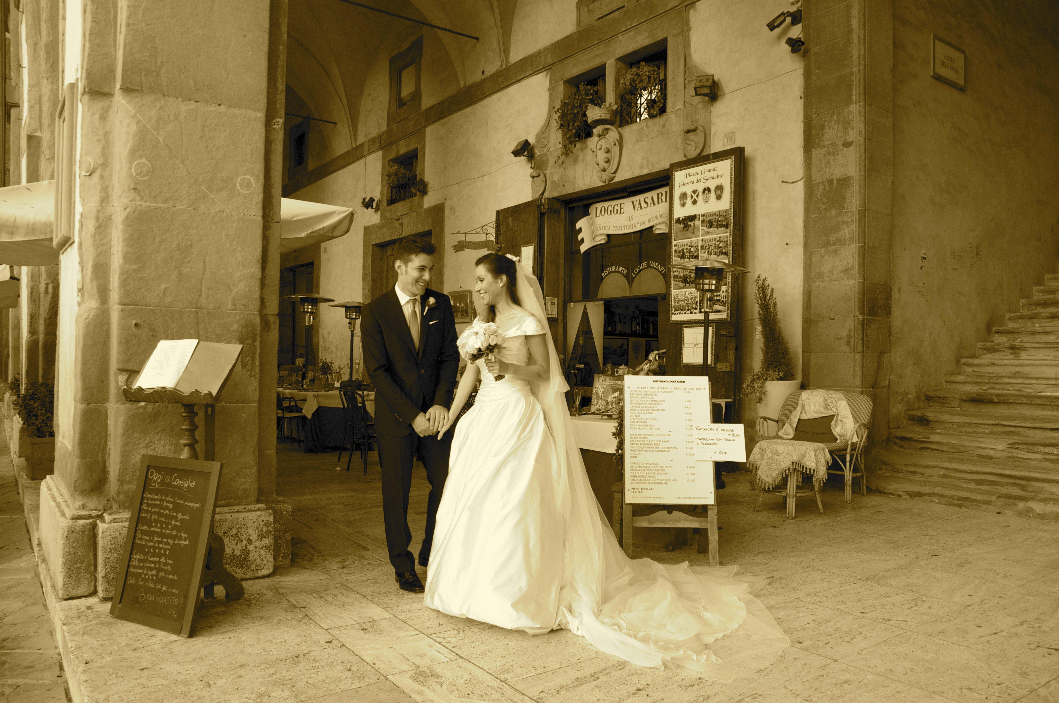 Foto di color seppia di sposi all'esterno di un negozio