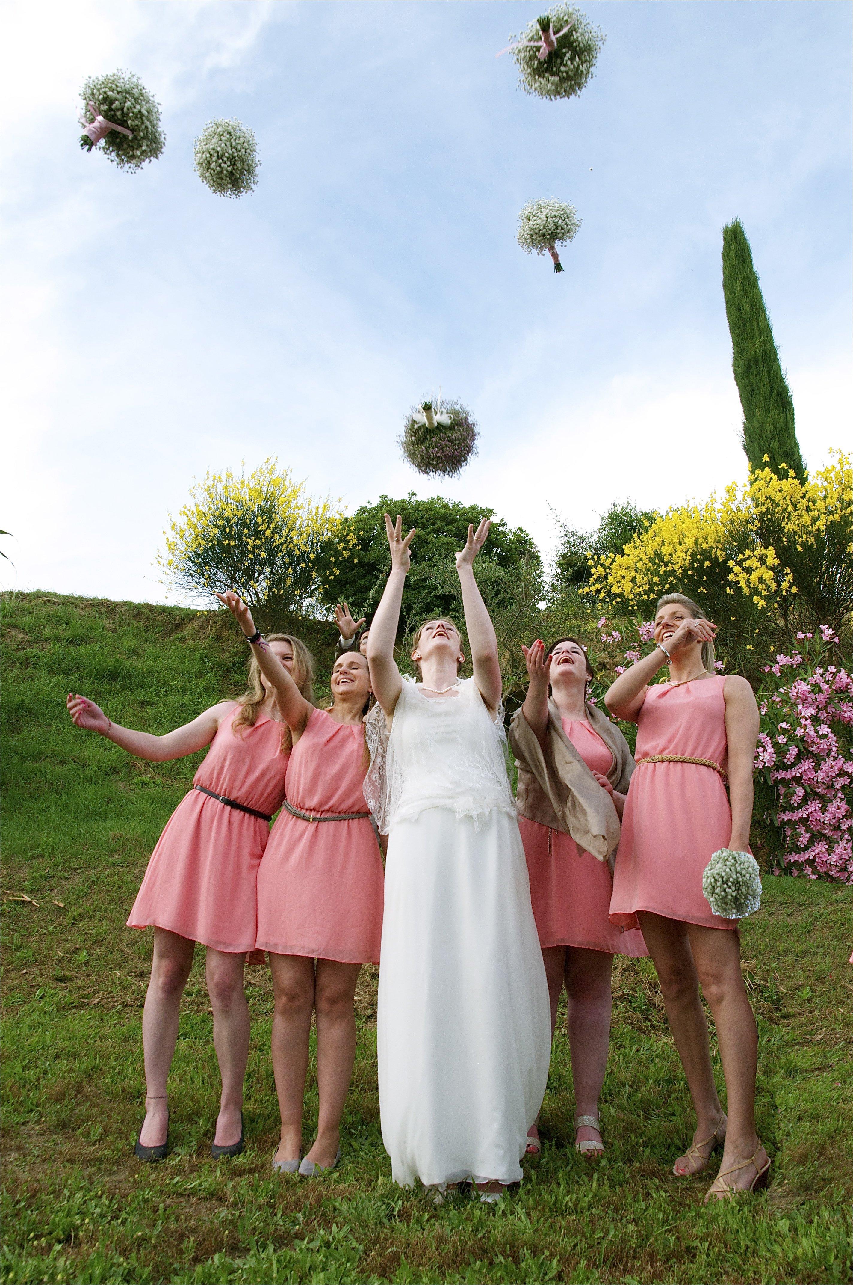 sposa in un giardino che lancia il bouquet insieme a quattro damigelle