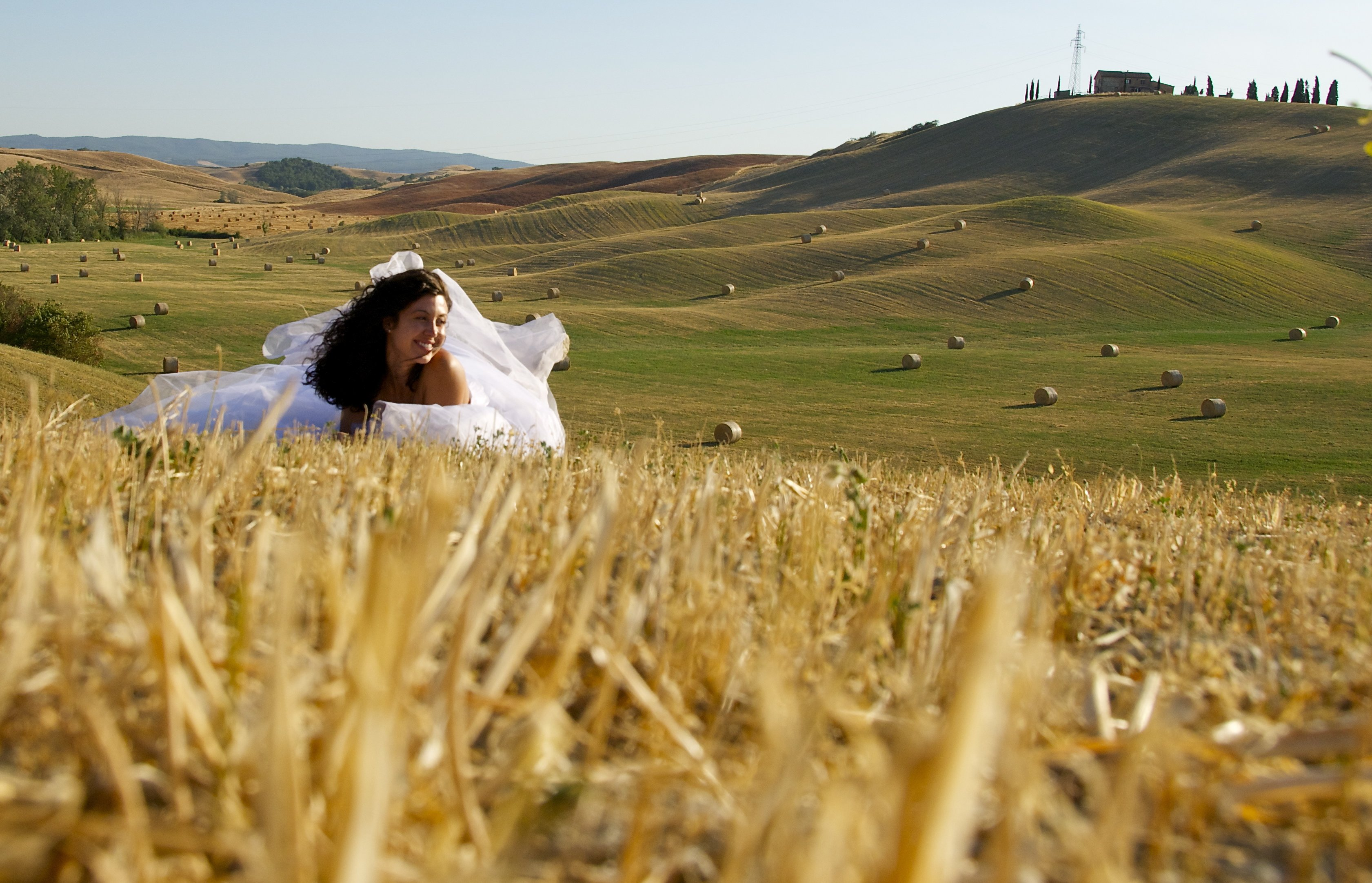 sposa in posa in un campo di grano trebbiato