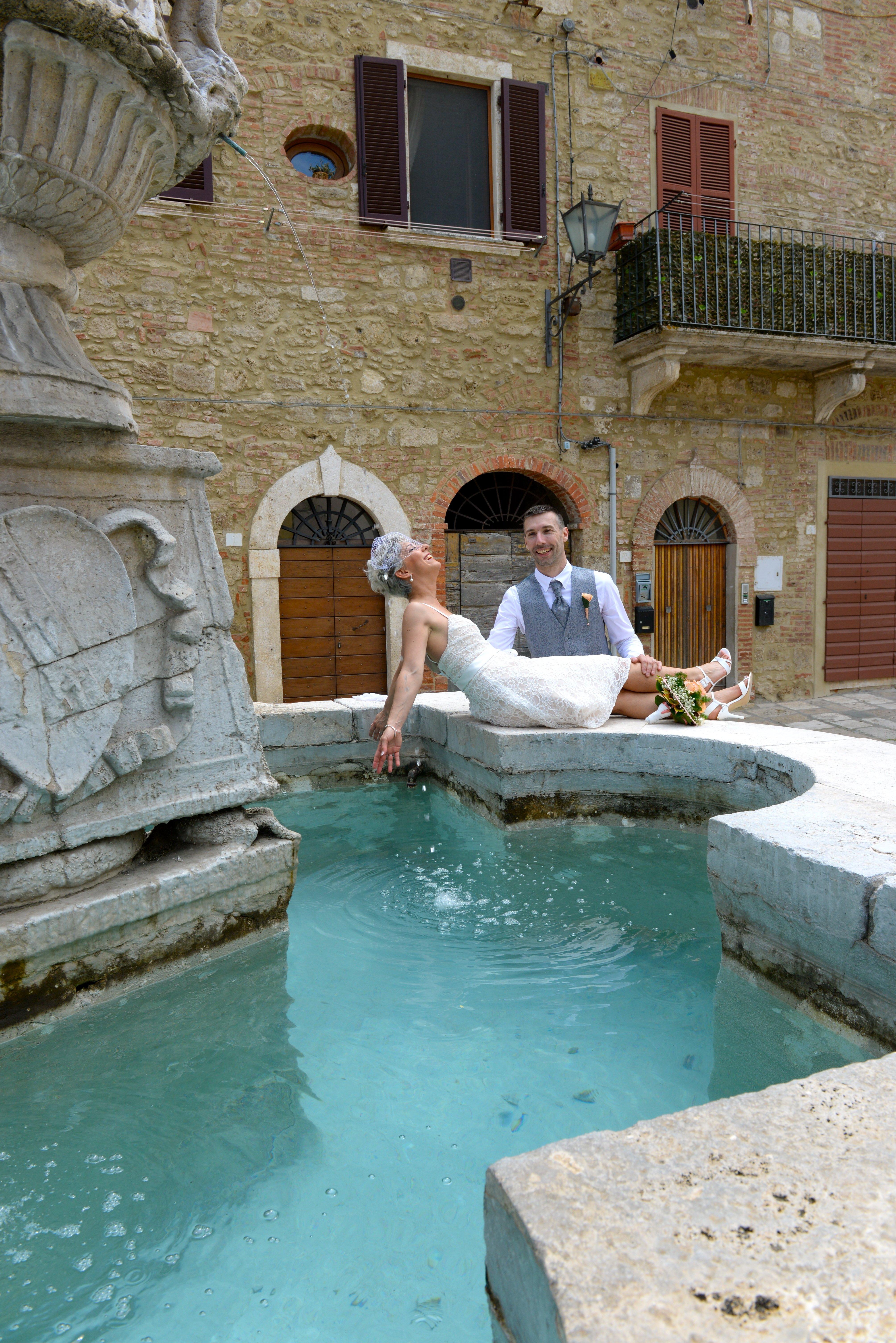 sposi giocano sull'orlo di una fontana nei pressi di un palazzo