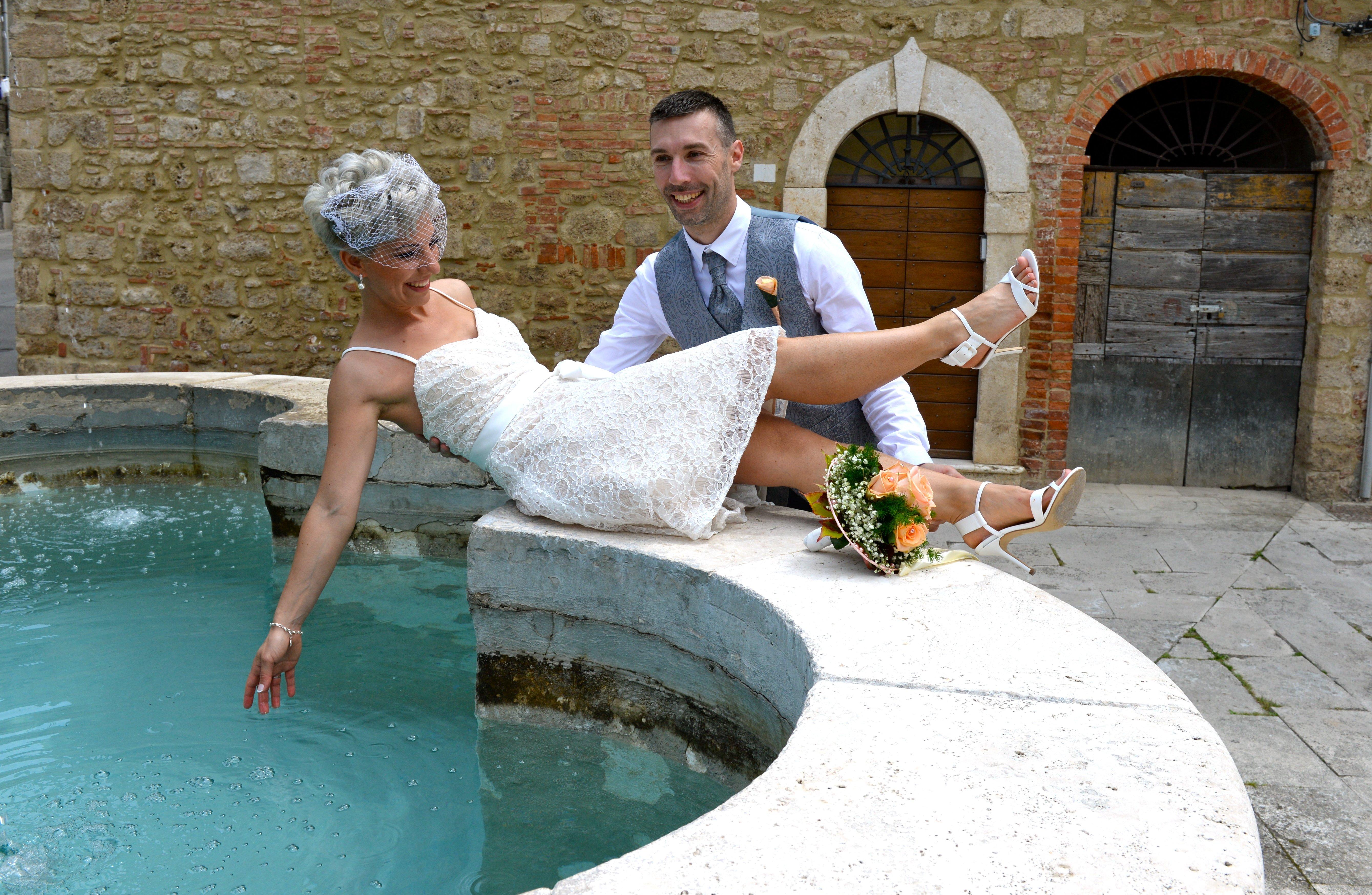 sposi giocano sull'orlo di una fontana in strada