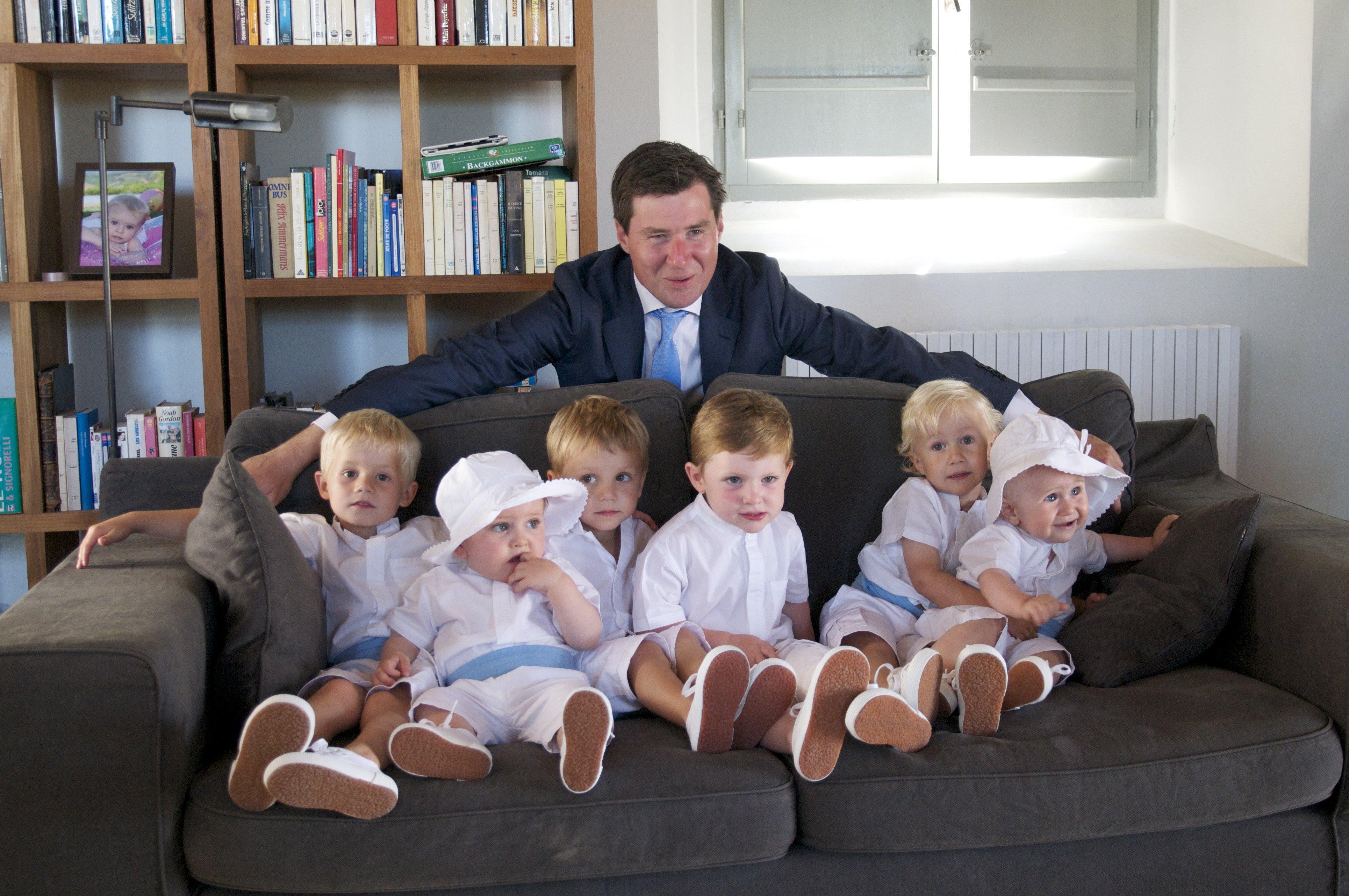 sposo abbraccia sei bambini seduti su un divano