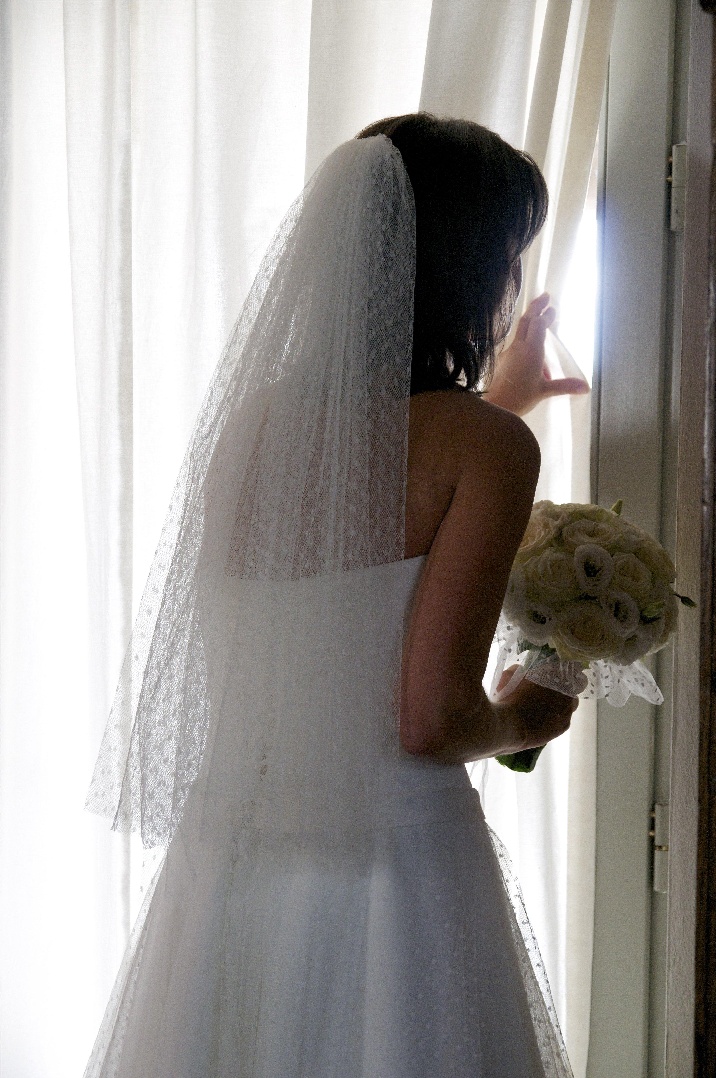sposa sbircia oltre le tende di una finestra