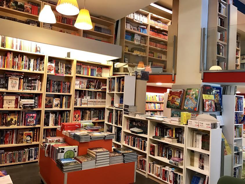 degli scaffali con dei libri esposti