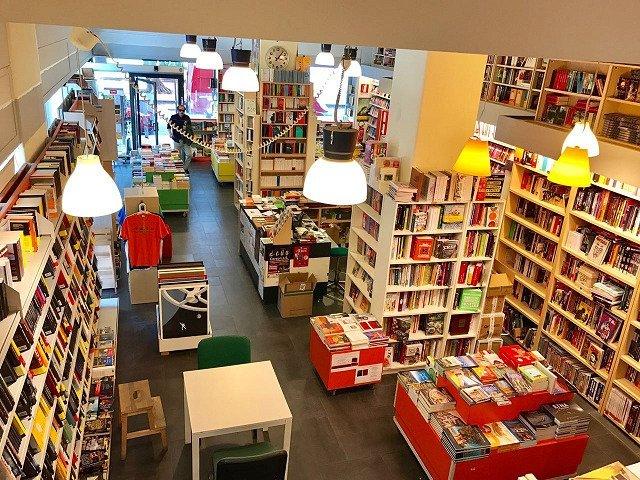 un tavolo con delle sedie e esposizione di libri in una libreria