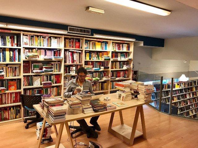 un uomo mentre legge un libro in una libreria