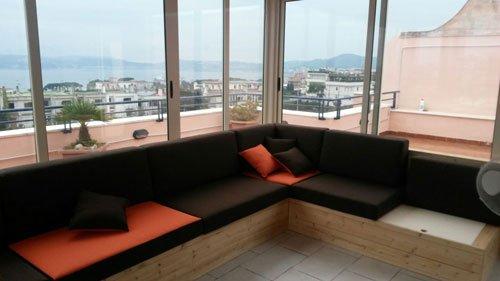 una panca-divano in legno angolare marrone scuro