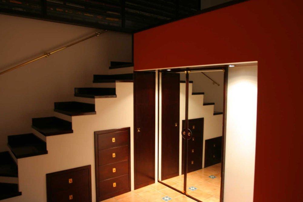 un armadio a specchio, dei cassetti marroni e dei gradini in legno scuro di una scala
