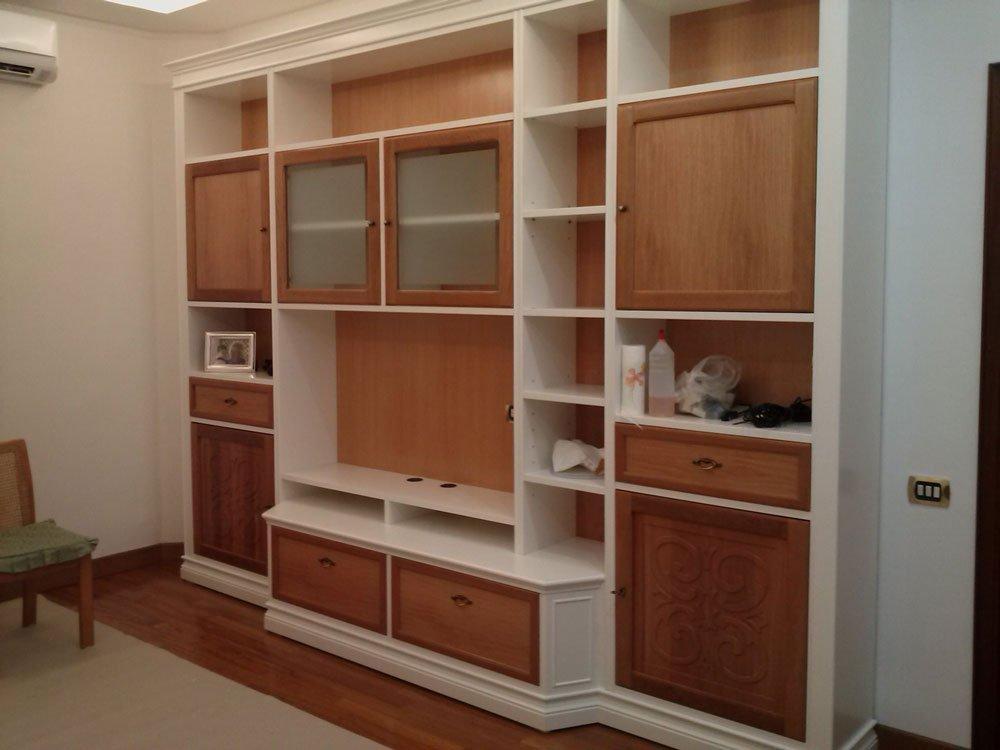 dei mobili in legno bianchi e marroni con al centro un alloggio tv