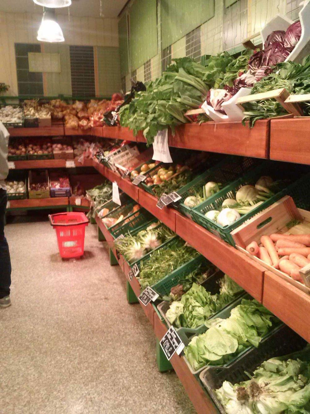 delle mensole in legno con delle cassette di frutta e verdura in un supermercato