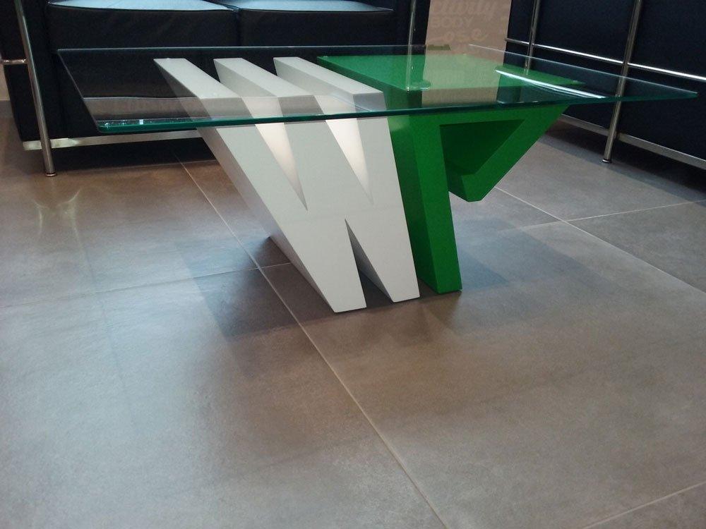 un tavolino di vetro e con la base in legno bianco e verde che formano le lettere W e P
