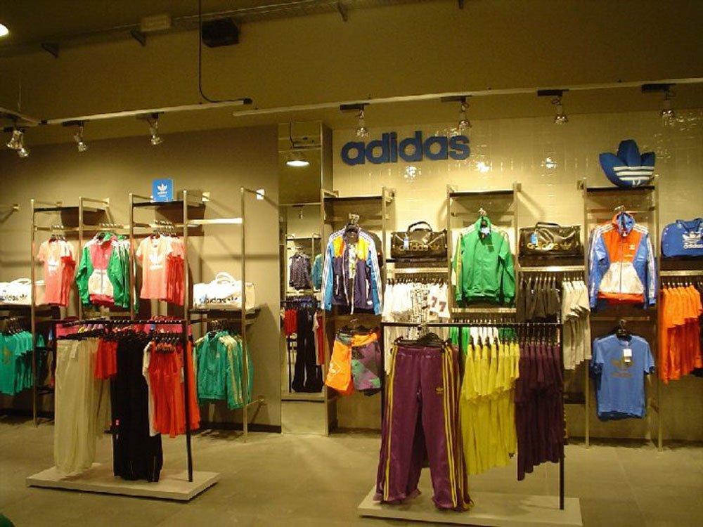 un negozio di vestiti con delle tute e altri capi e la scritta sul muro Adidas