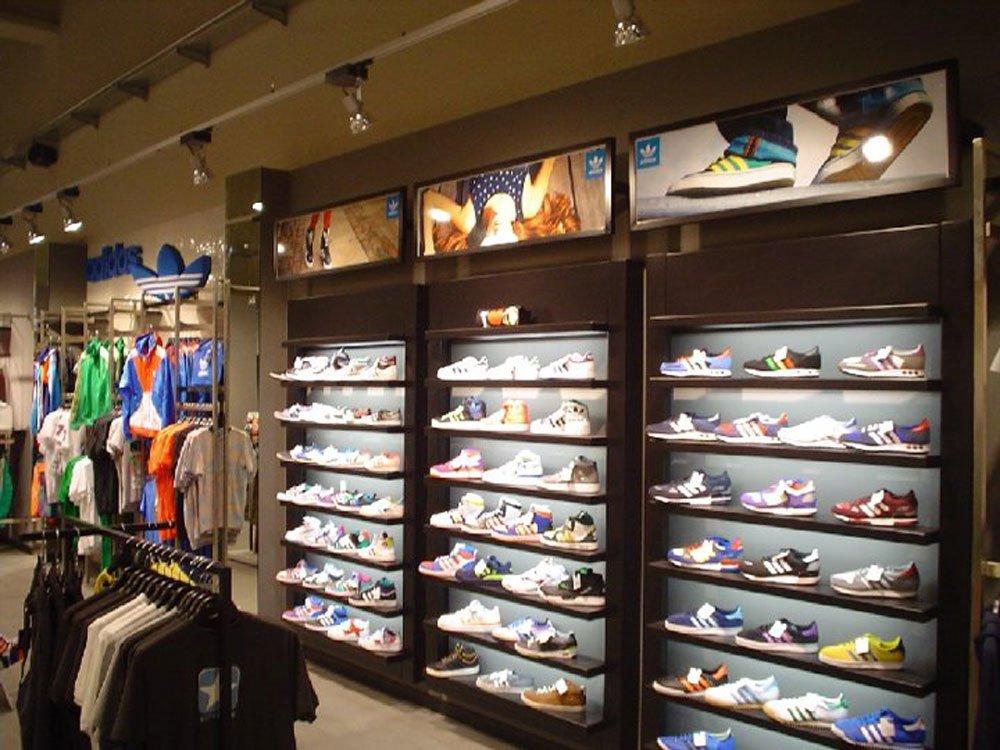 un pannello di legno con delle piccole mensole con delle scarpe Adidas in esposizione