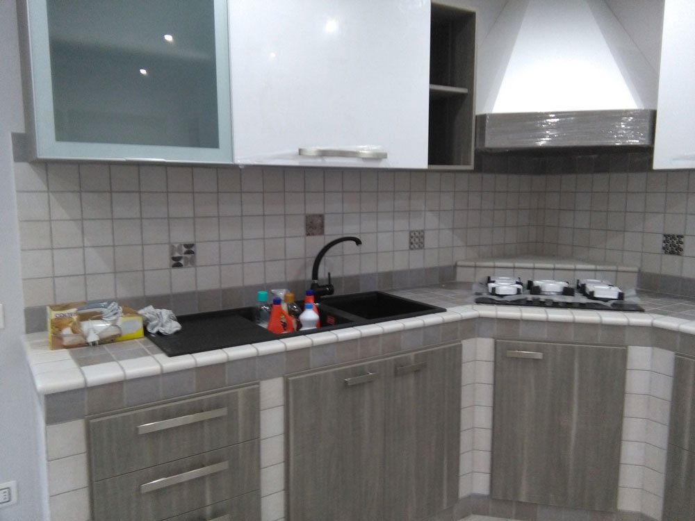una cucina con mobili color panna e grigio