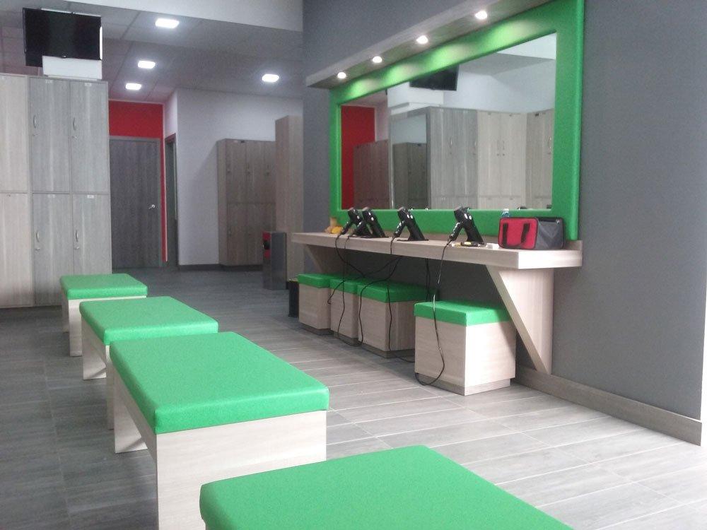 delle piccole panche in legno e di pelle verde in un negozio di parrucchieri