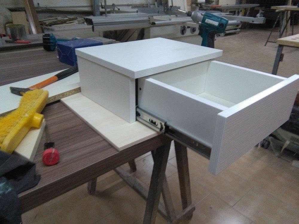 un cassetto aperto di color bianco su un banco da lavoro in una falegnameria