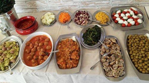 un buffet con dei vassoi di piatti a base di carne e contorno di verdura