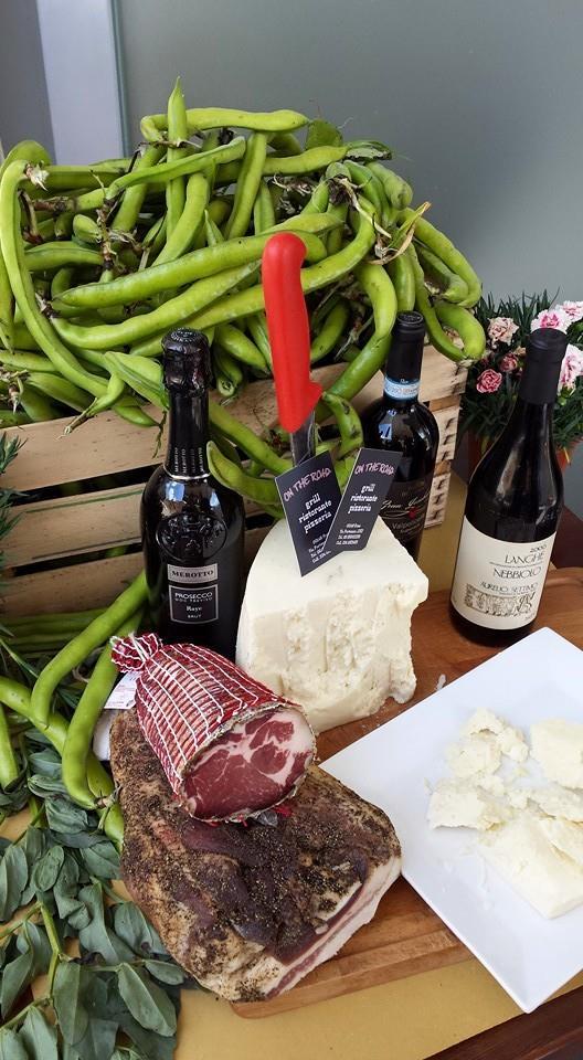 un tagliere con dei tranci di carne, formaggio e due bottiglie di vino