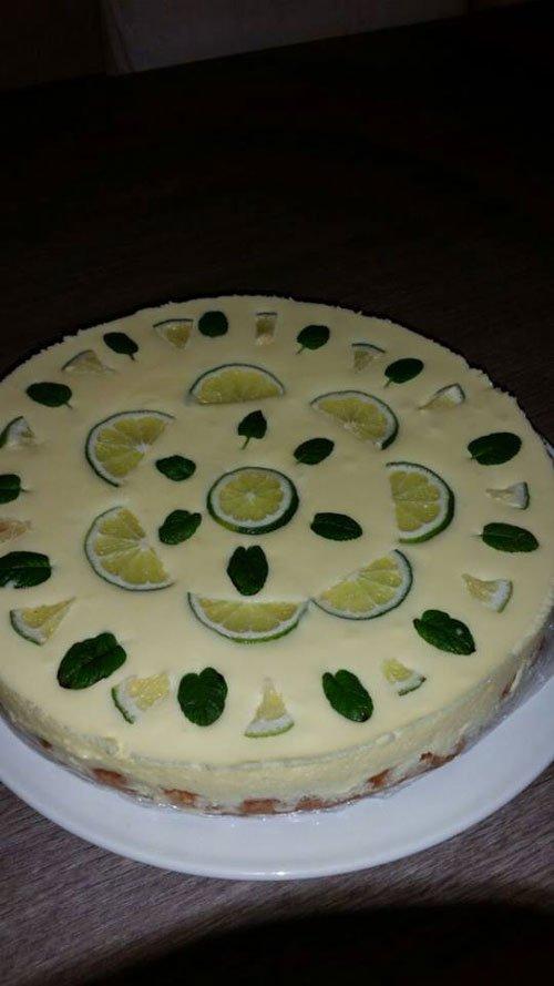 una cheesecake con fette di lime e foglie di menta