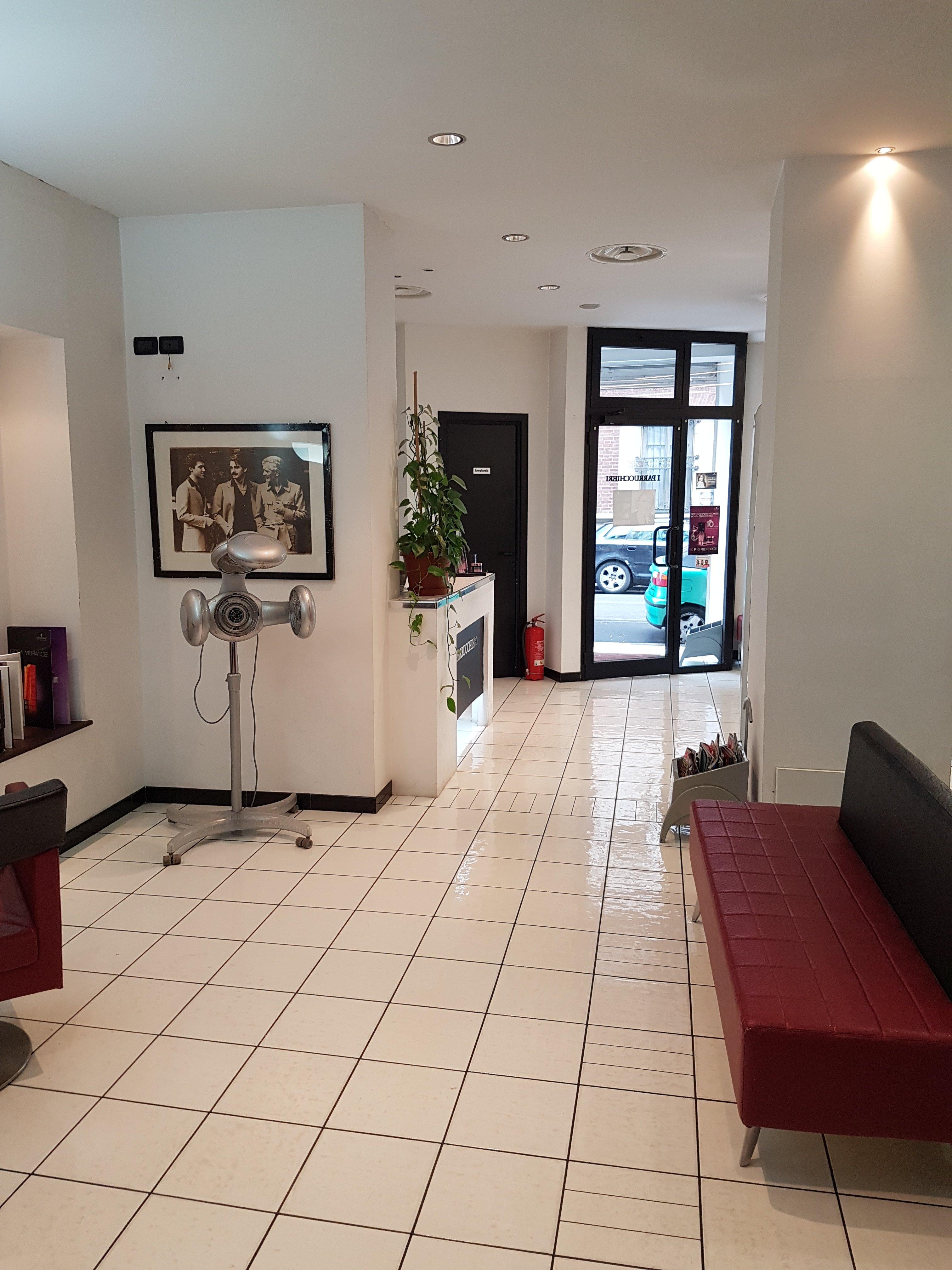 interno di sala di attesa di parrucchiere con divano rosso