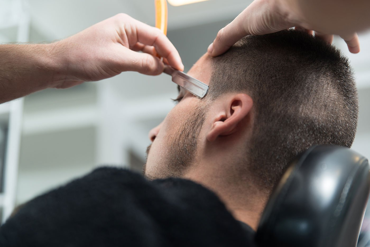 Un parrucchiere mentre sistema acconciatura di un uomo con uno razzaio
