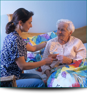 A lady helping an elderly lady eat her meal in bed