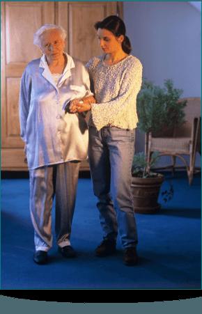 A woman helping an elderly lady walk in her pyjamas