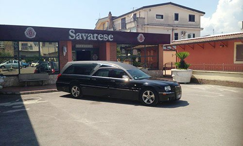 Un carro funebre di color nero e vista del cielo azzurro