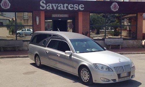 Un carro funebre grigio davanti a un ufficio