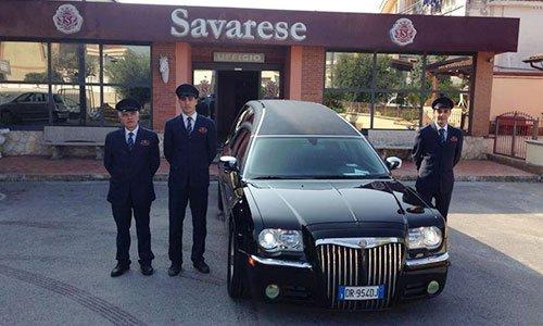 Un carro parcheggiato davanti un ufficio e accanto tre uomini con completo nero