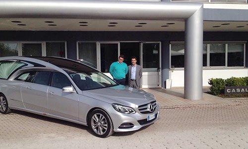 Un carro funebre di color grigio della marca Mercedes