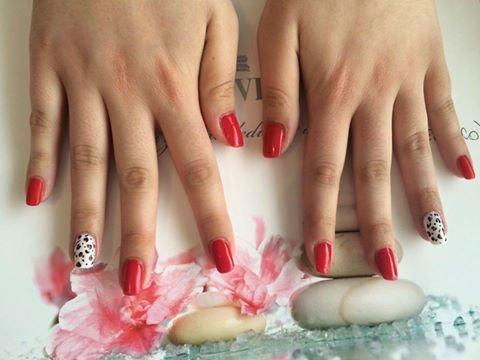 delle unghie con dello smalto rosso e bianco a disegni neri