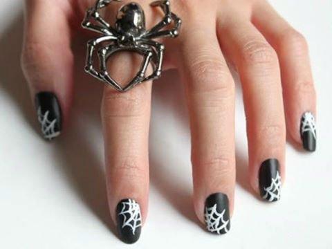 delle unghie di color nero con dei disegni a ragnatele bianche