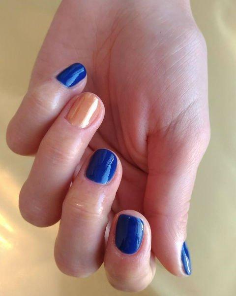 delle mani con le unghie blu e arancioni