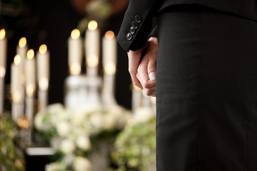 vista delle mani di un uomo in piedi con un completo nero e davanti delle candele accese