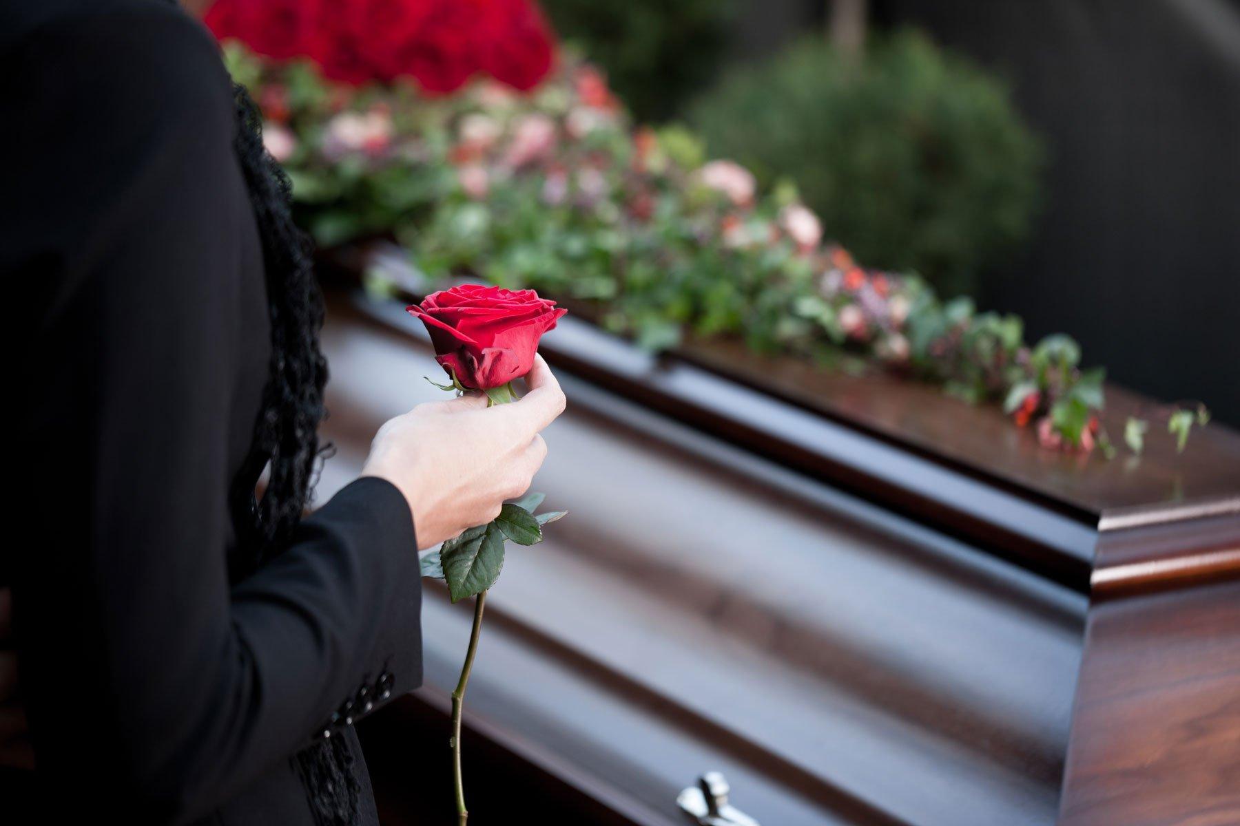 una donna con in mano una rosa rossa davanti a una bara in legno con sopra dei fiori