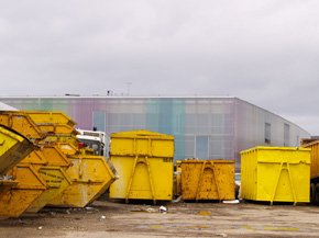 A yard with different size yellow skips in