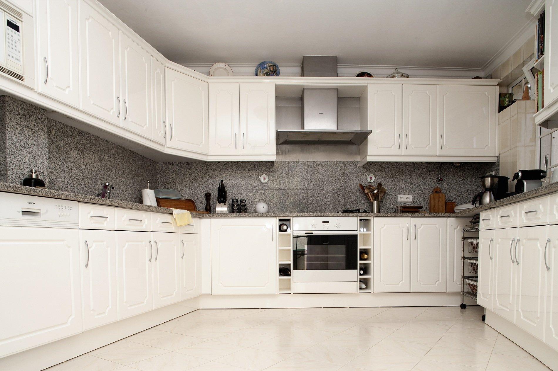 una cucina angolare con mobili bianchi