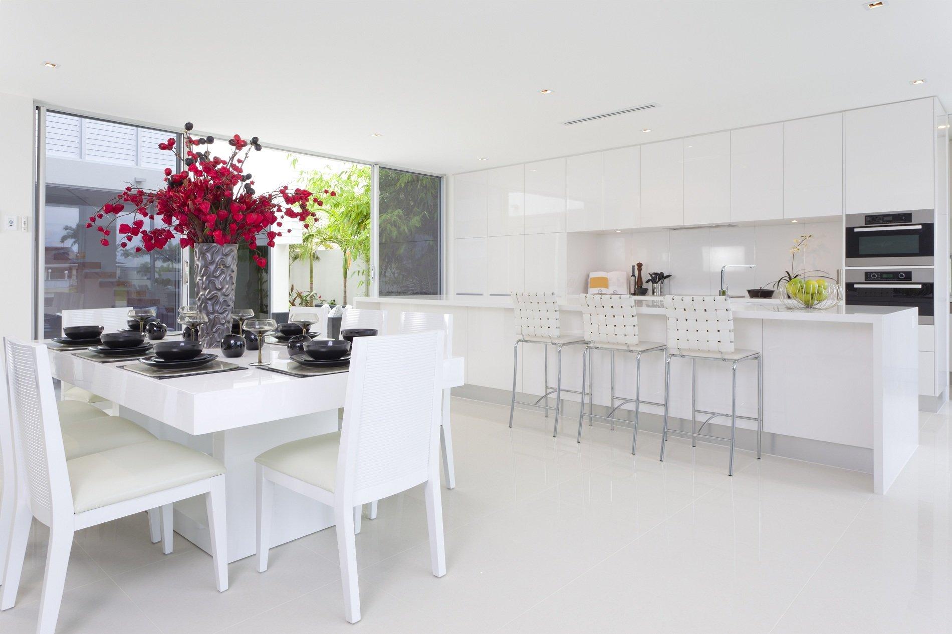 un'ampia cucina con mobili bianchi tre sedie alte e un tavolo con delle sedie