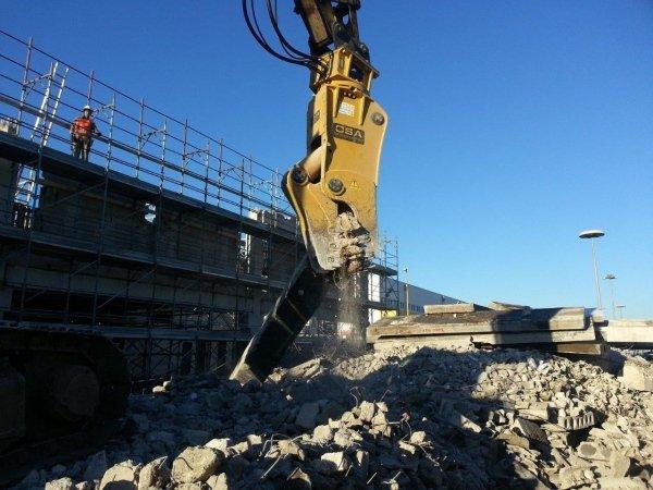 frantumazione mediante pinza dei bloccchi e residui della demolizione a taglio della copertura di uno dei depositi del CIS di Nola