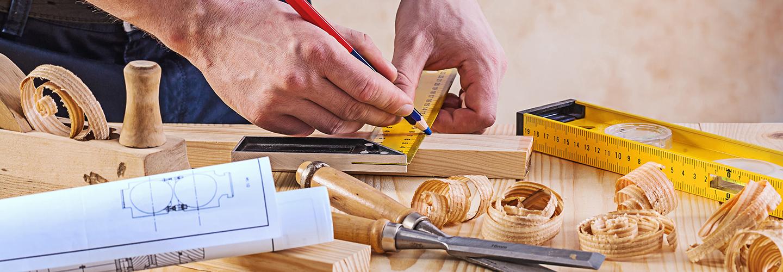 falegname che prende le misure su un pezzo di legno