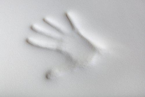 mano mentre testa la morbidezza di un materasso