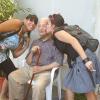 anziano con zanetta seduto su una sedia  mentre viene baciato da una ragazza