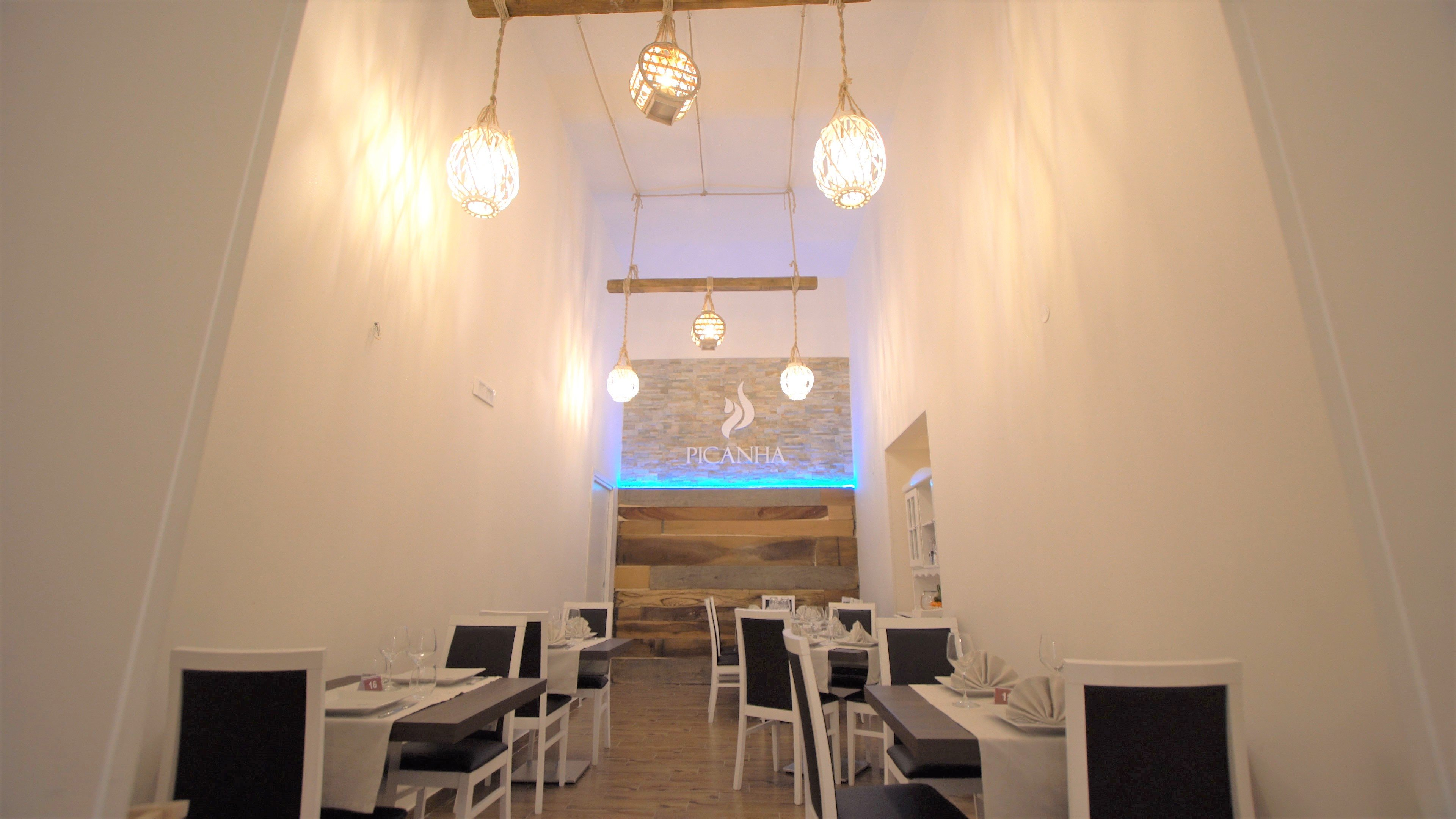 sala ristorante con pareti pianche alte e tavoli apparecchiati